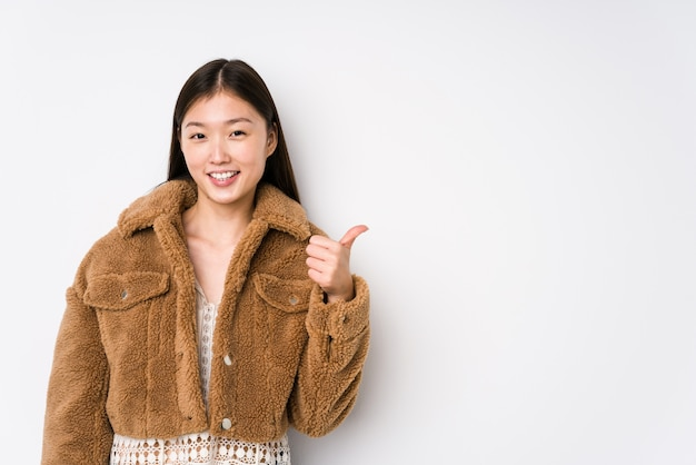 Young chinese woman posing in a white wall isolated smiling and raising thumb up