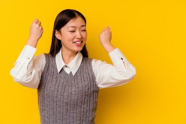 승리, 승자 개념 후 주먹을 올리는 젊은 중국 여자. 프리미엄 사진
