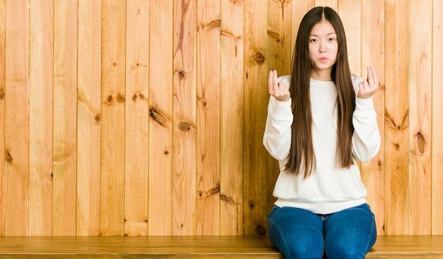 Молодая китаянка сидит на деревянном месте, показывая, что у нее нет денег.