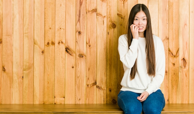 Young chinese woman sitting a wooden place biting fingernails, nervous and very anxious.