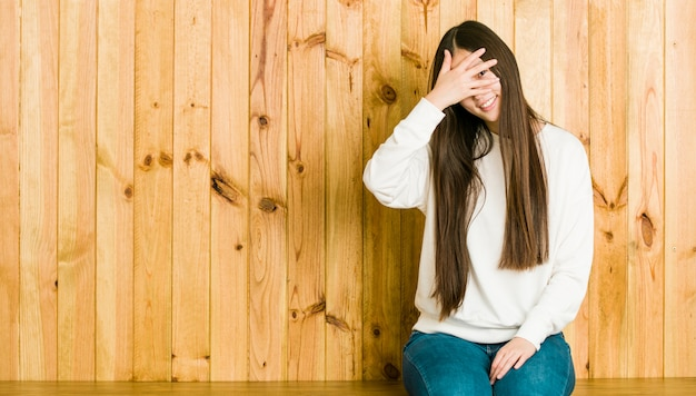 Young chinese woman sitting on a wooden place blink at the camera through fingers, embarrassed covering face.