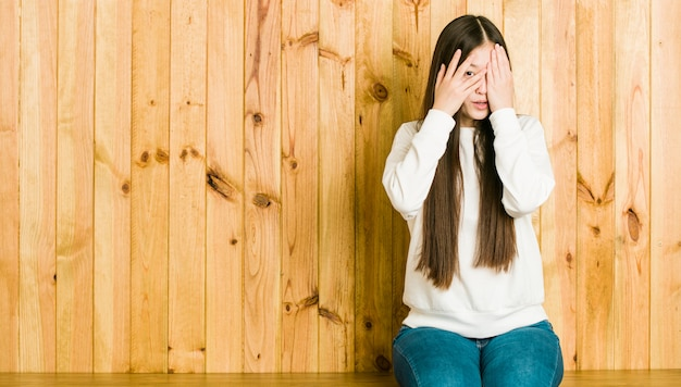 Young chinese woman sitting on a wooden place blink through fingers frightened and nervous.