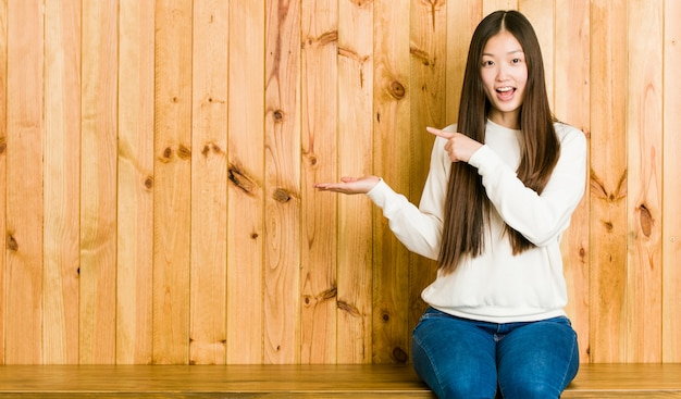 Young chinese woman sitting on a wooden place excited holding a copy space on palm.