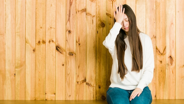 Young chinese woman sitting on a wooden place forgetting something, slapping forehead with palm and closing eyes.