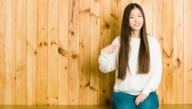 Young chinese woman sitting on a wooden place person pointing by hand to a shirt copy space, proud and confident