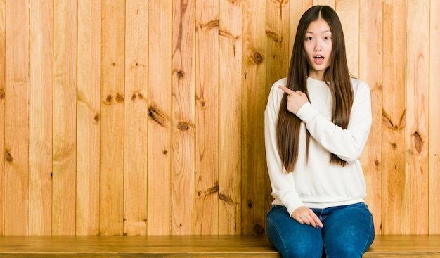 Young chinese woman sitting on a wooden place pointing at something to the side