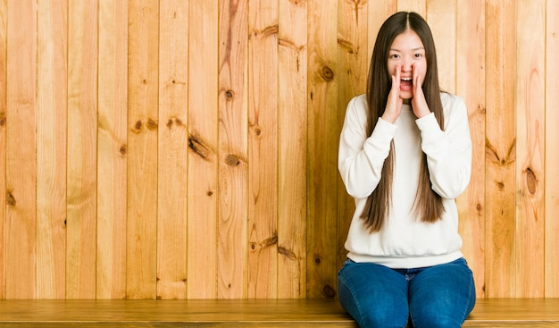 Young chinese woman sitting on a wooden place shouting excited to front.