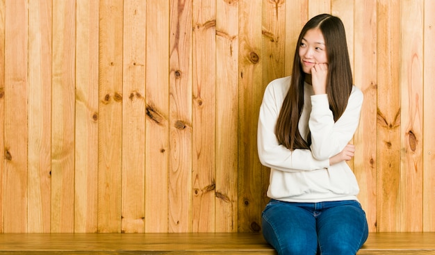 Young chinese woman sitting on a wooden place who feels sad and pensive, looking at copy space.