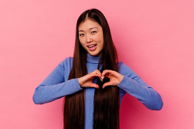 웃 고 손으로 심장 모양을 보여주는 젊은 중국 여자.