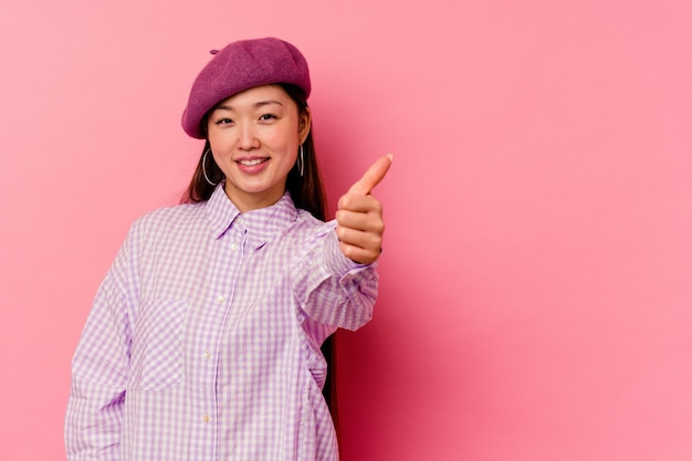 Young chinese woman   smiling and raising thumb up