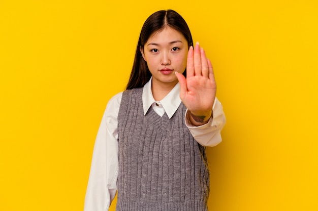 Young chinese woman  standing with outstretched hand showing stop sign, preventing you.