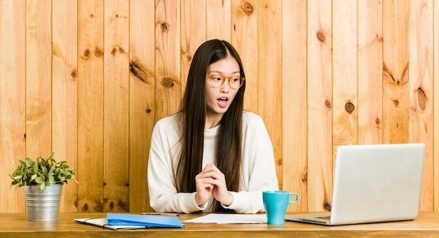 Young chinese woman studying on her desk being shocked because of something she has seen.