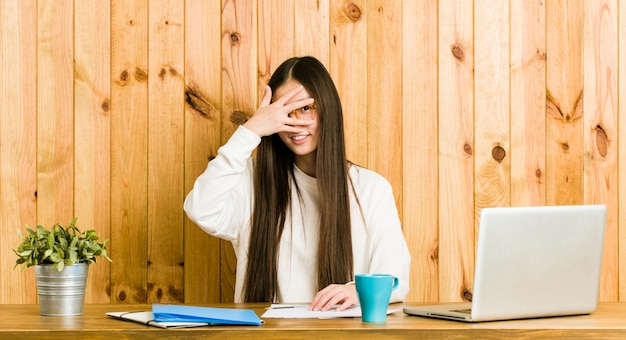 Young chinese woman studying on her desk blink at the camera through fingers, embarrassed covering face.