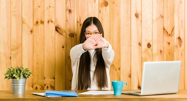 Young chinese woman studying on her desk doing a denial gesture