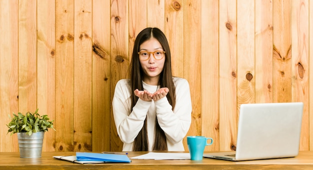 Young chinese woman studying on her desk folding lips and holding palms to send air kiss.