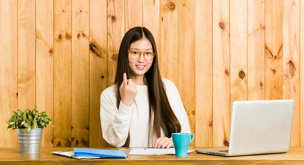 Young chinese woman studying on her desk pointing with finger at you as if inviting come closer.