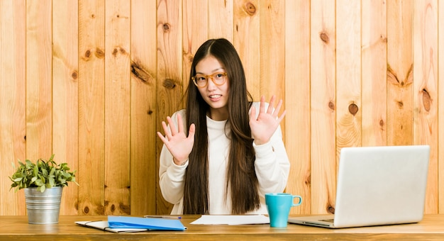 Young chinese woman studying on her desk rejecting someone showing a gesture of disgust.