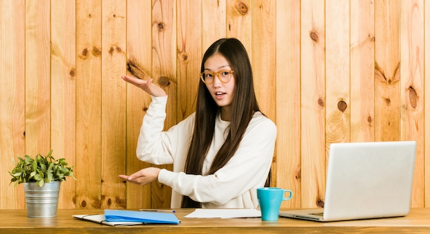 Young chinese woman studying on her desk shocked and amazed holding a  between hands.