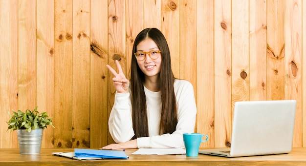 Young chinese woman studying on her desk showing number two with fingers.