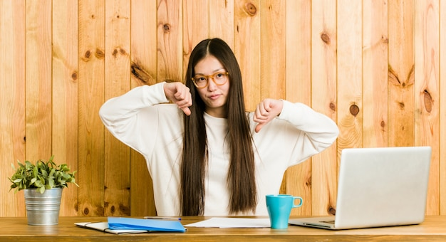 Young chinese woman studying on her desk showing thumb down and expressing dislike.
