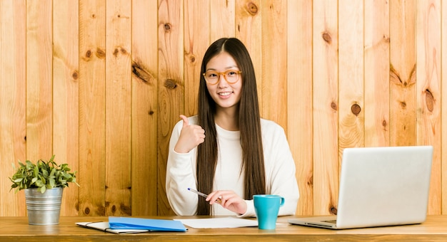 Young chinese woman studying on her desk smiling and raising thumb up
