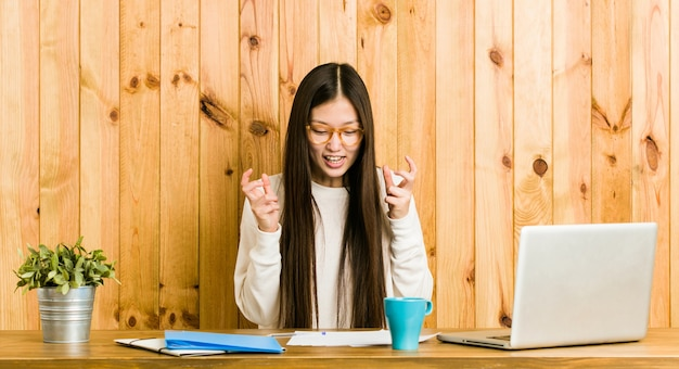 Young chinese woman studying on her desk upset screaming with tense hands.