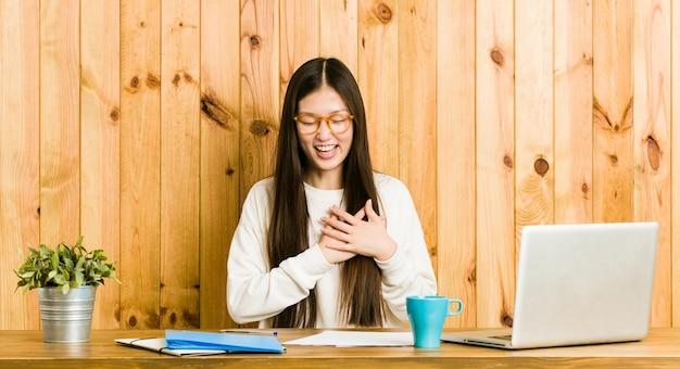 心に手を置いて笑って、幸せの概念、彼女の机で勉強している若い中国人女性。