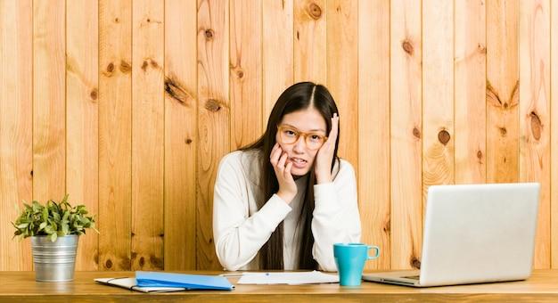 Молодая китаянка учится на своем столе, ноет и безутешно плачет.