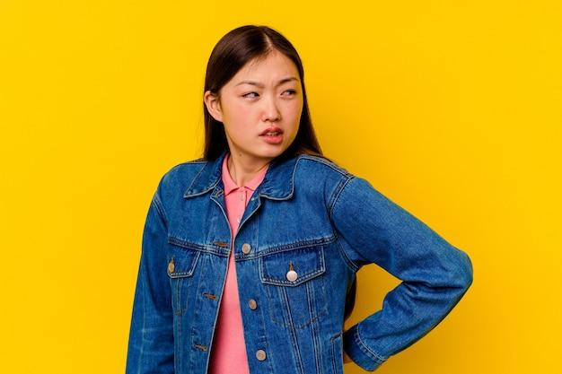 背中の痛みに苦しんでいる若い中国人女性。