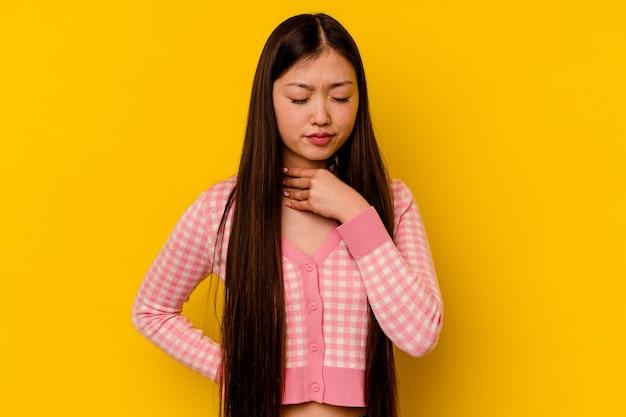 若い中国人女性は、ウイルスや感染症のために喉の痛みに苦しんでいます。