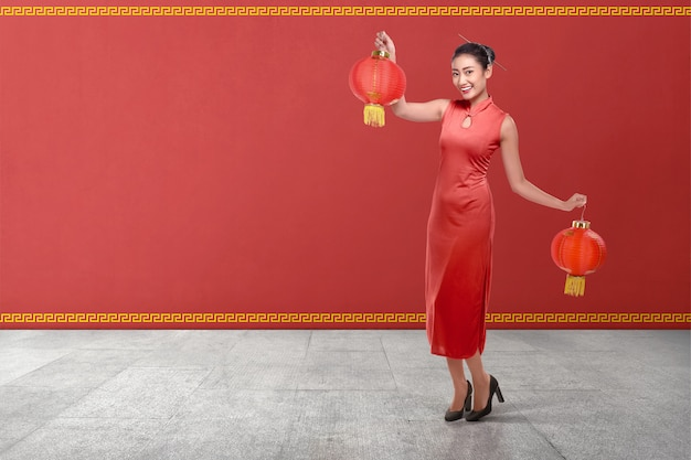 Young chinese woman in a traditional clothing holding red lanterns