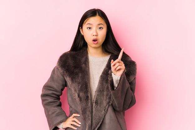 Молодая китаянка в пальто изолирована, имея идею, концепцию вдохновения.