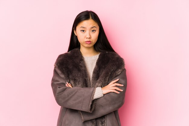 皮肉な表情でカメラで見て不幸なコートを着ている若い中国人女性。