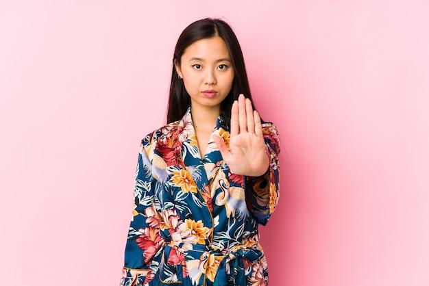 기모노 파자마를 입고 젊은 중국 여자는 당신을 방지하는 정지 신호를 보여주는 뻗은 손으로 서 고립.