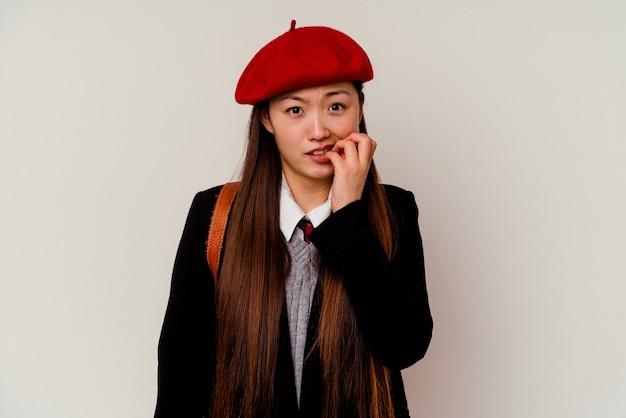 Молодая китаянка в школьной форме на белом фоне кусает ногти, нервничает и очень тревожится.