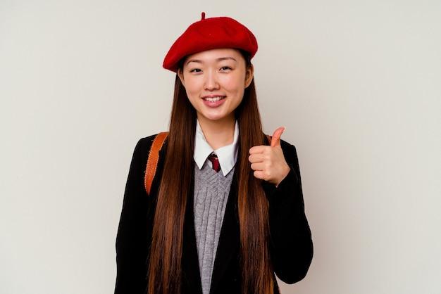 Молодая китаянка в школьной форме на белом фоне улыбается и поднимает палец вверх