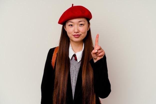 손가락으로 번호 하나를 보여주는 흰색 절연 학교 유니폼을 입고 젊은 중국 여자.