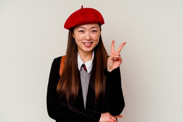 Молодая китаянка в школьной форме, изолированной на белом, показывает номер два пальцами.