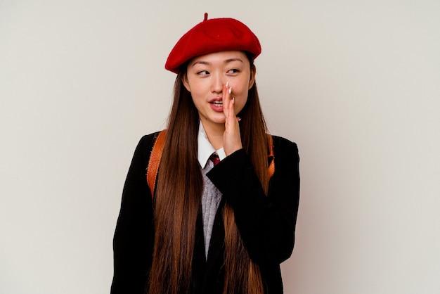 白い壁に隔離された制服を着た若い中国人女性が秘密の熱いブレーキングニュースを言って脇を見ている