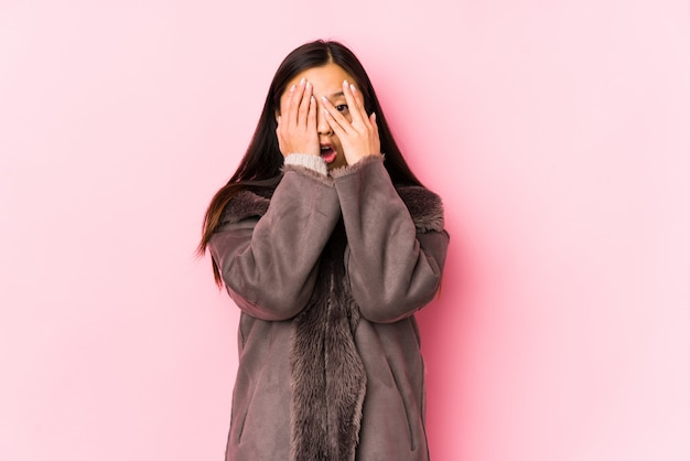 Young chinese woman wearing a coat isolated blink through fingers frightened and nervous.