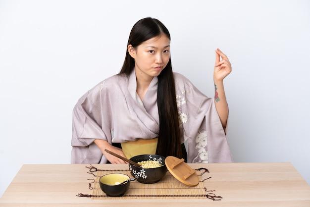기모노를 입고 이탈리아 제스처를 만드는 국수를 먹는 젊은 중국 여자