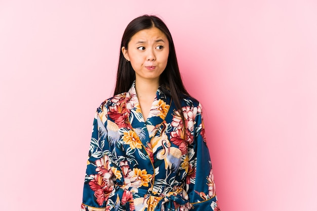 Young chinese woman wearing a kimono pajama isolated confused, feels doubtful and unsure.