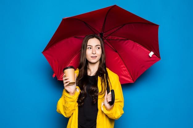 孤立した青い壁に傘を持ってレインコートを着ている若い中国人女性手と指で非常に幸せなポインティング