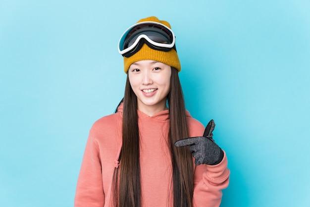 シャツのコピースペースを手で指しているスキー服孤立した人を着ている若い中国人女性、誇りと自信