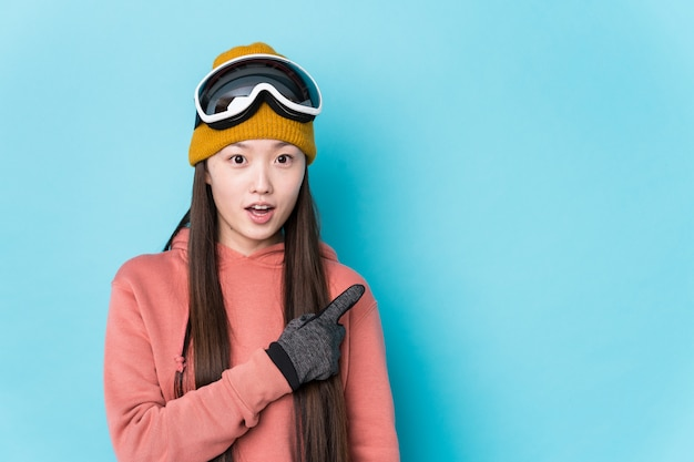 Young chinese woman wearing ski clothes isolated pointing to the side