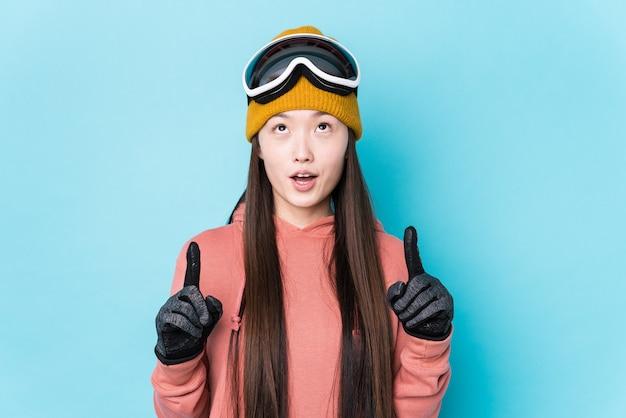 口を開けて逆さまに指している分離されたスキー服を着ている若い中国人女性。
