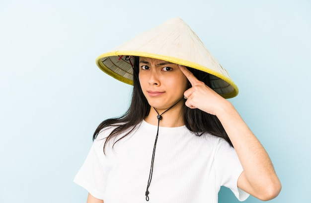 Young chinese woman wearing a vietnamese hay isolated pointing with finger at you as if inviting come closer.