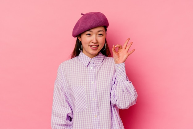Young chinese woman  winks an eye and holds an okay gesture with hand.