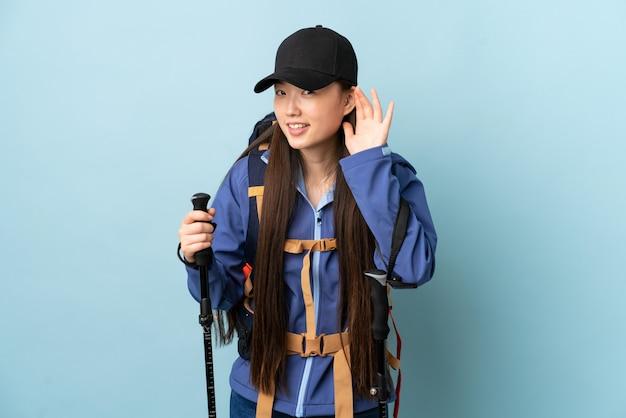 バックパックと耳に手を置くことによって何かを聞いて孤立した青い壁にトレッキングポールを持つ若い中国人女性