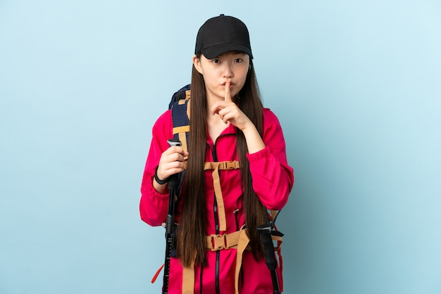 Young chinese woman with backpack and trekking poles over isolated blue wall showing a sign of silence gesture putting finger in mouth